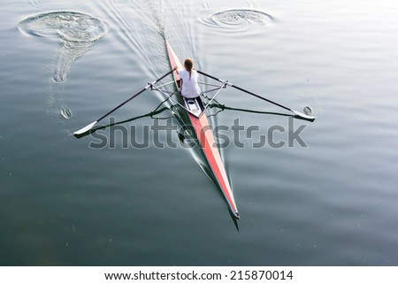 A young woman in a boat, paddles on the tranquil lake  - stock photo