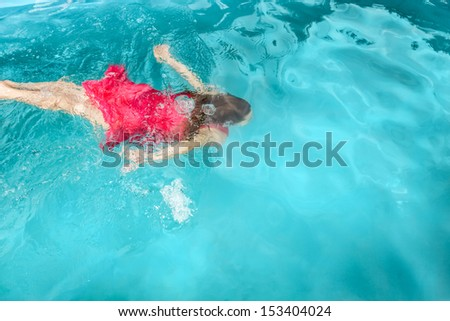 A young woman in a red dress swimming under water in the pool