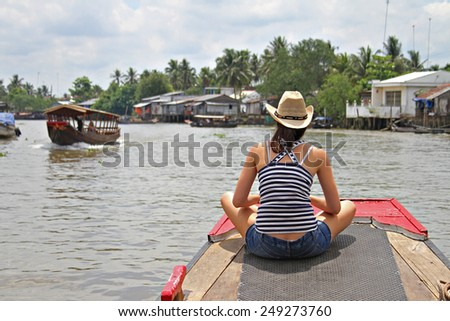 A young woman in a straw hat rides a boat up the Mekong River in Vietnam. - stock photo