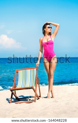 A young woman in a swimsuit relaxing on a deckchair on the beach - stock photo