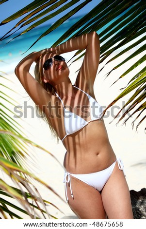 A young woman in a white bikini standing on a beach among palm trees - stock photo