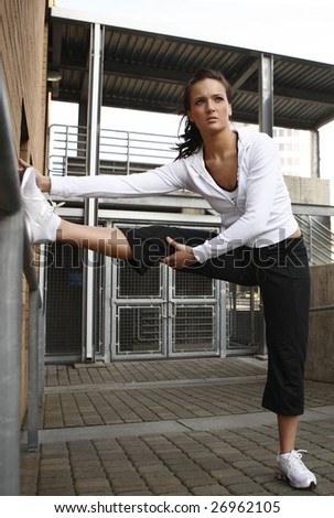 A young woman in fitness clothes stretching on a hand rail.
