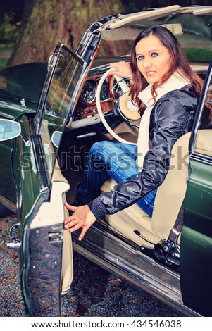 A young woman in front of Post-War classic car