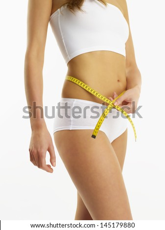 A young woman in her underwear holding a measuring tape, against white background - stock photo