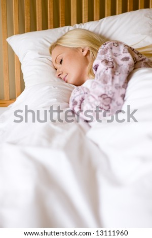A young woman in pyjamas asleep in bed