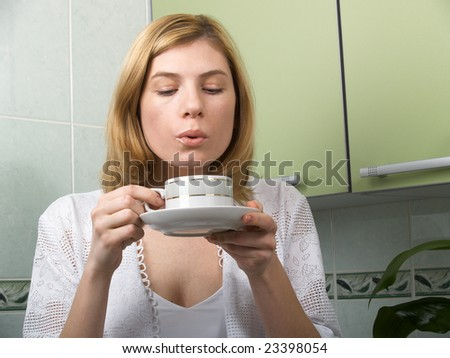 A young woman in the kitchen drinking coffee