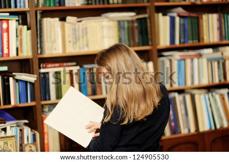 A young woman in the library reading a book - stock photo