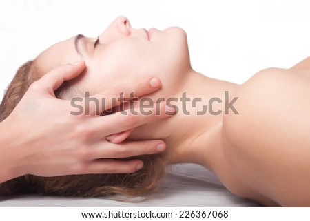 a young woman is being treated by a masseuse - stock photo