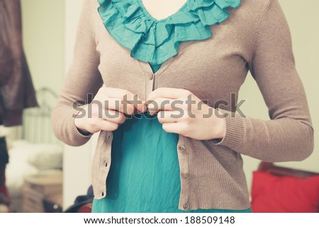 A young woman is buttoning her blouse - stock photo