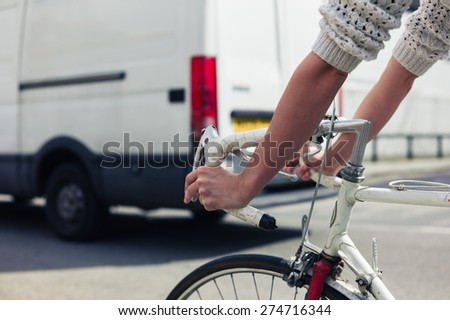 A young woman is cycling on the road in a city on a sunny day