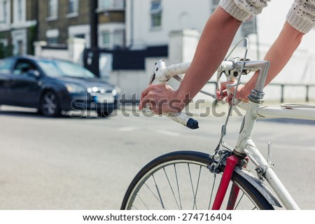 A young woman is cycling on the road in a city on a sunny day - stock photo