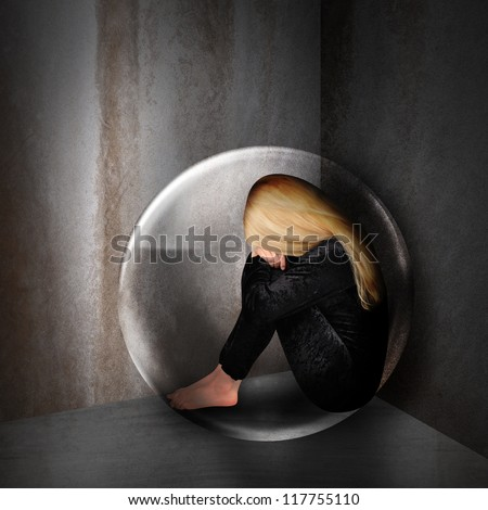 A young woman is depressed and sad in a bubble in a dark room. The girl has her head down and curled up in a corner.