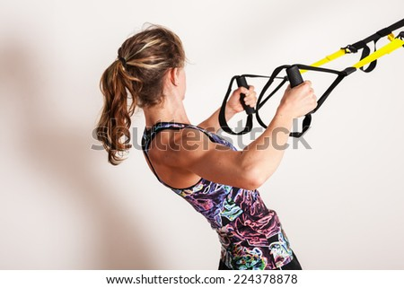 A young woman is doing bodyweight rows with straps - stock photo