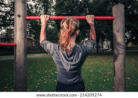 A young woman is doing pull ups in the park - stock photo