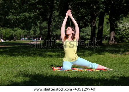 A young woman is engaged in yoga in the park