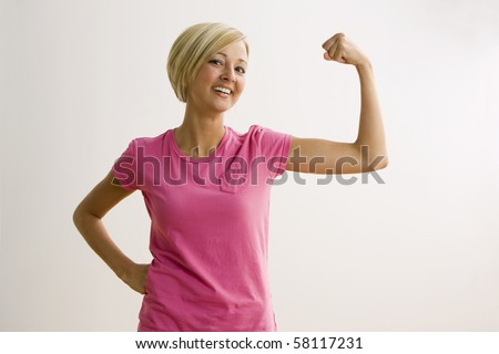 A young woman is flexing her bicep and smiling at the camera.  Horizontal shot.