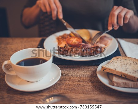 A young woman is having a traditional english breakfast with bacon and eggs