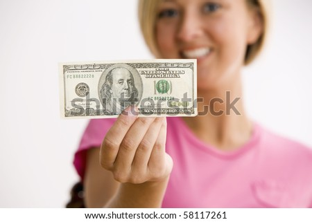 A young woman is holding out a $100.00 bill and smiling at the camera.  Horizontal shot.