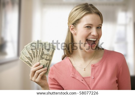 A young woman is holding up cash in a fan and smiling at the camera.  Horizontal shot.