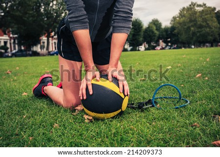 A young woman is in the park with a medicine ball and a resistance band