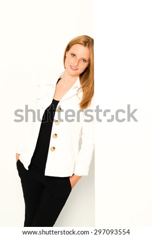 A young woman is leaning against an empty whitw wall with copy space - bright studio shot - stock photo