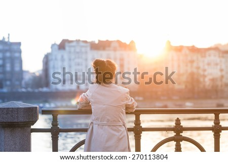 A young woman is looking at the sunset over a river in the city Prague with the old buildings in the background. Soft spring backlit. Color toned image. - stock photo