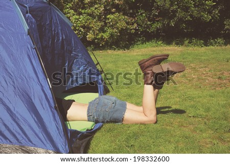 A young woman is lying in a tent with her legs sticking out