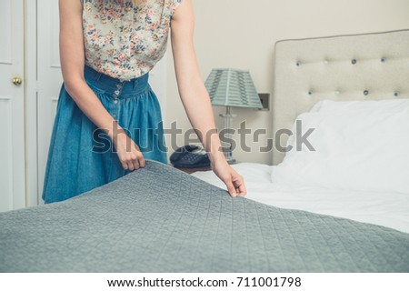 A young woman is making the bed in a hotel room