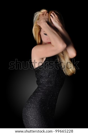 A young woman is moving and has curve shape on a black background. She is hiding her face and has blond hair. - stock photo
