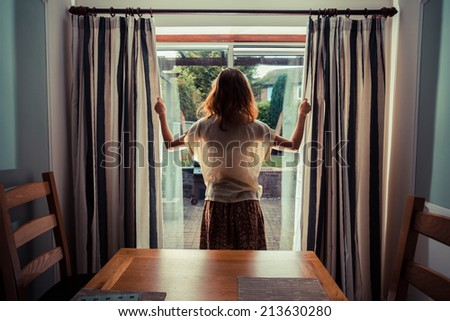 A young woman is opening the curtains at sunrise - stock photo