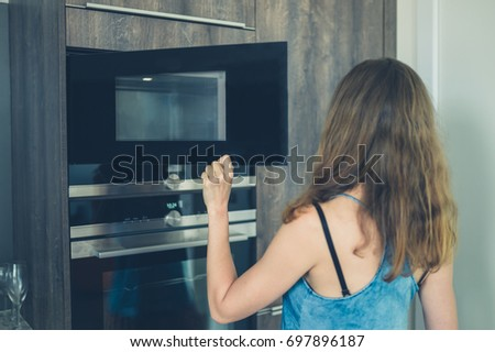 A young woman is opening the microwave in her modern apartment