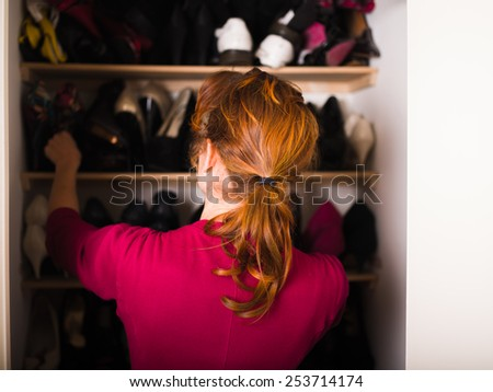 A young woman is organizing her shoe cupboard at home - stock photo