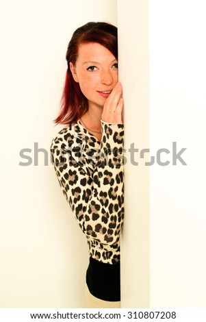 A young woman is peeking around an empty white wall - bright studio shot - stock photo