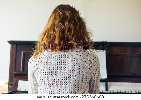 A young woman is playing the piano - stock photo