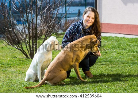 A young woman is playing with pets in the garden