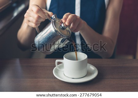 A young woman is pouring herself a cup of coffee in a diner - stock photo