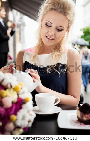 A young woman is pouring tea. Holding a cup of tea. Outdoors - stock photo