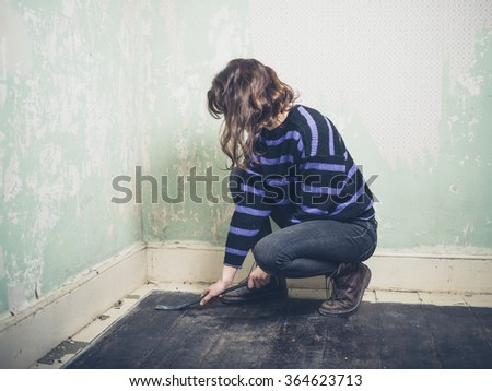 A young woman is prying the nails in her floorboards with a crowbar