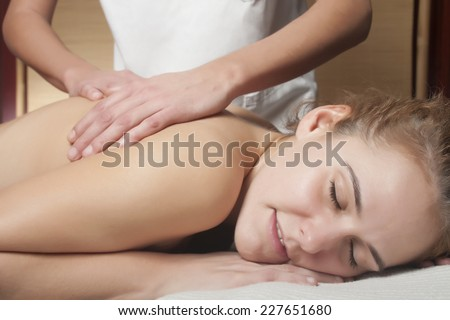 a young woman is receiving a massage, as anti-stress treatment