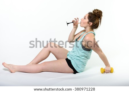 A young woman is reclining with a hand weight in one hand and wine in her other hand. She is drinking the wine. Shot on a seamless white studio backdrop. - stock photo