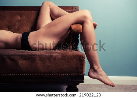 A young woman is relaxing on a sofa