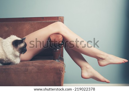 A young woman is relaxing on a sofa with a cat - stock photo