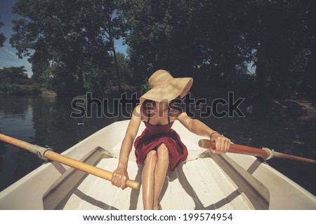 A young woman is rowing a boat on a summer day - stock photo