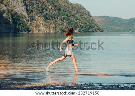 A young woman is runing on a tropical beach - stock photo