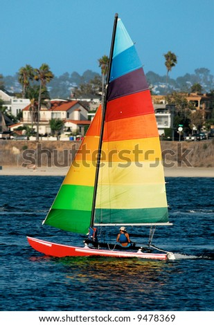 A young woman is sailing in Mission Bay, San Diego. A colorful yacht with rainbow-colored sail stands out against a background of out-of-focus suburban houses...