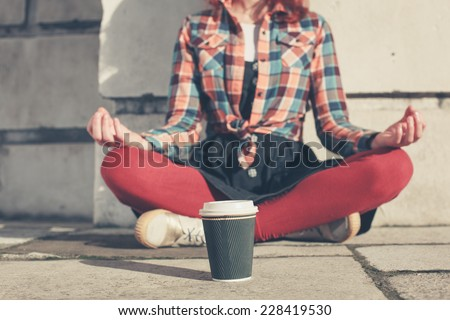 A young woman is sitting and meditating in the street - stock photo