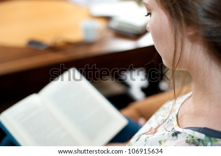 A young woman is sitting and reading a book. - stock photo