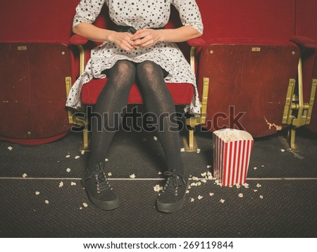 A young woman is sitting in a movie theater with popcorn on the floor - stock photo