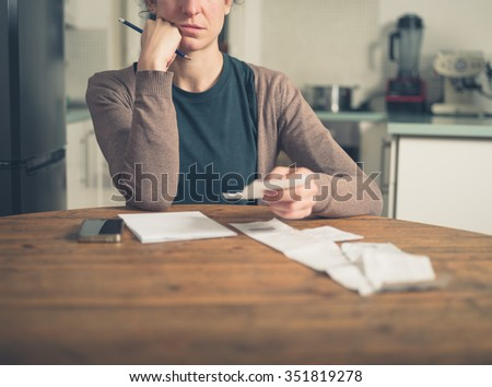 A young woman is sitting in her kitchen and is looking at her receipts at home while using a smart phone - stock photo