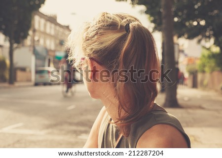 A young woman is sitting in the street looking at the traffic - stock photo